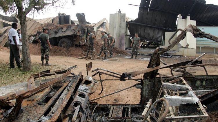 Des soldats français dégagent les débris de l'épave d'un véhicule blindé au lycée Descartes de Bouaké, qui servait de base aux soldats français, le10 novembre 2004. (PHILIPPE DESMAZES / AFP)