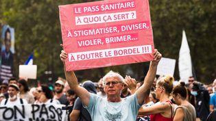 """Un manifestant tient une pancarte avec le message """"Le pass sanitaire, à quoi ça sert ?"""" à Paris, le 4 septembre 2021. (AMAURY CORNU / HANS LUCAS / AFP)"""
