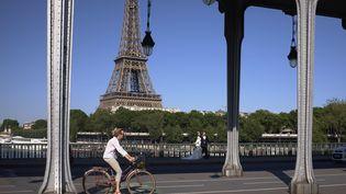 Une femme fait du vélo à Paris, le 8 juin 2017. (BLANCHOT PHILIPPE / HEMIS.FR)