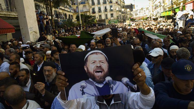 Contestation du Hirak pour l'élection présidentielle en Algérie. Un manifestant brandit une photo d'Abassi Madani, l'ancien leader du Front Islamiquedu Salut (FIS) mort en exil au Qatar. Photo prise le 27 avril 2019. (RYAD KRAMDI / AFP)