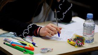 Une lycéenne passe le bac de philosophie le 18 juin 2018 au lycéeFresnel de Caen. (CHARLY TRIBALLEAU / AFP)