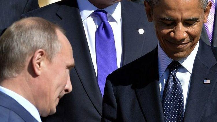 Président de la Russie Vladimir Poutine (G) passe devant le président américain Barack Obama afin de poser pour la photo de famille lors du sommet du G20, le 6 Septembre 2013, à Saint-Pétersbourg. (AFP PHOTO / JEWEL SAMAD)