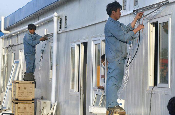 Des ouvriers réalisant des finitions sur le nouvel hôpital de Xiaotangshan, dans la banlieue de Pékin, construit pour soigner les malades atteints du Sras, le 29 avril 2003. (FREDERIC BROWN / AFP)