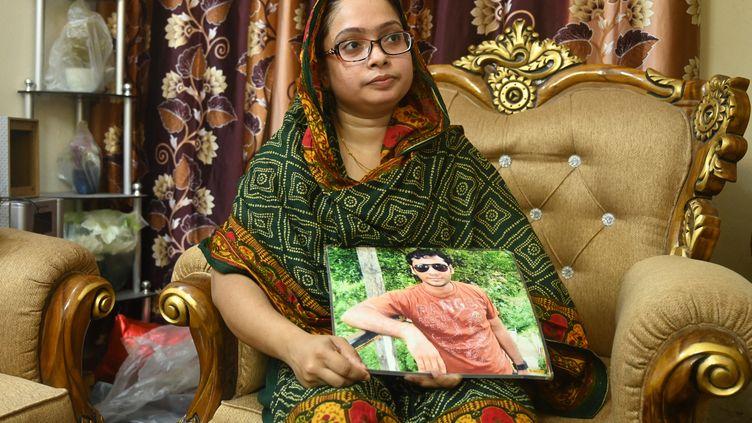 Une femmetient une photo de son mari, membre du Parti nationaliste duBangladesh, disparu en 2013,le 14 août 2021, à Dacca. (MUNIR UZ ZAMAN / AFP)
