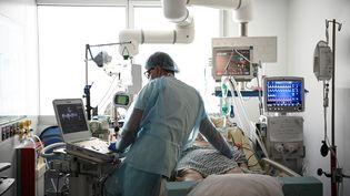 Un membre de l'unité de soins intensifs de l'hôpital Georges Pompidou à Paris au chevet d'un patient, le 6 avril 2021. (ANNE-CHRISTINE POUJOULAT / AFP)