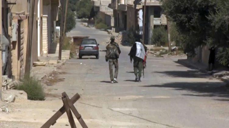 Deux soldats syriens patrouillent dans les rues de la ville d'al-Qaryatayne, dans le centre de la Syrie, le 21 octobre 2017, après sa reprise au groupe Etat islamique. (AP / SIPA)