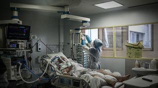 Une soignante s'occupe d'un patient atteint du Covid-19 dans la section de réanimation de l'hôpital Robert Boulin à Libourne(Gironde), le 6 novembre 2020 (photo d'illustration). (PHILIPPE LOPEZ / AFP)