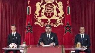 Le roi du Maroc,Mohammed VI, lors d'un discours le 20 août 2019, entouré par son fils le prince Moulay Hassan à sa droite et son frère le prince Moulay Rachid à sa gauche. (- / MAP / AFP)