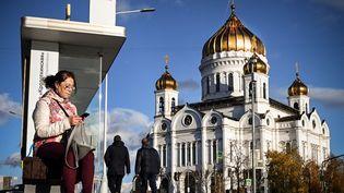 Une femme devant la Cathédrale du Christ Sauveur à Moscou (Russie), le 18 octobre 2021. (ALEXANDER NEMENOV / AFP)