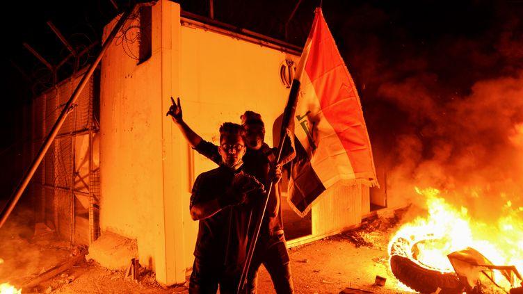 Des manifestants irakiens devant le consulat iranien en flammes, le 27 novembre 2019, à Najaf. (AFP)