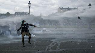 Un militantlance un projectile vers les forces de l'ordre, lors de la manifestation contre la loi Travail à Paris, le 14 juin 2016. (MICHAEL BUNEL / NURPHOTO / AFP)
