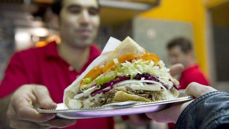 Un homme sert un döner kebab dans un restaurant à Berlin (Allemagne), le 21 mars 2010. (GERO BRELOER / AP / SIPA)
