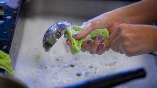 Une femme lave un ustensile dans un évier. (Illustration) (GAETAN BALLY / MAXPPP)