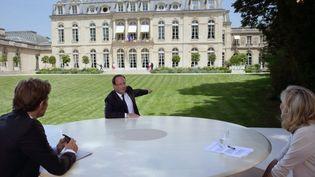 François Hollande discute avec Laurent Delahousse (gauche) et Claire Chazal (droite), après l'interview du dimanche 14 juillet 2013 au Palais de l'Elysée (Paris). (PHILIPPE WOJAZER / AFP)