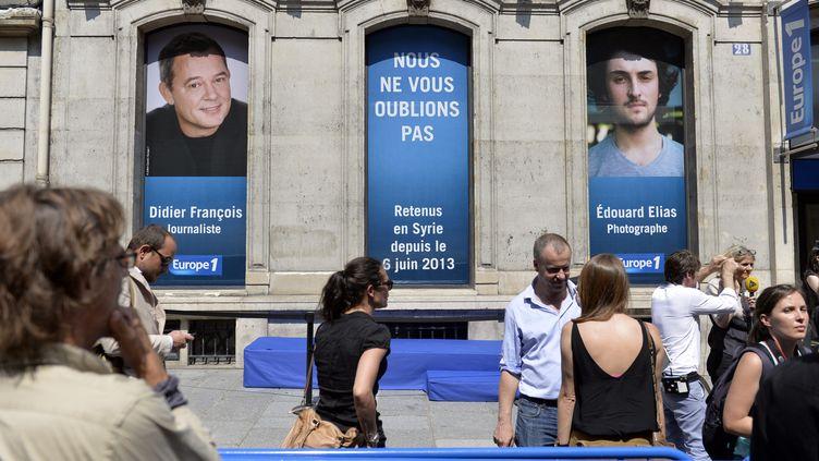Des portraits de Didier François et Edouard Elias sont affichés aux fenêtres d'Europe 1 lors d'un rassemblement de soutien, le 9 juillet 2013 à Paris. (ERIC FEFERBERG / AFP)
