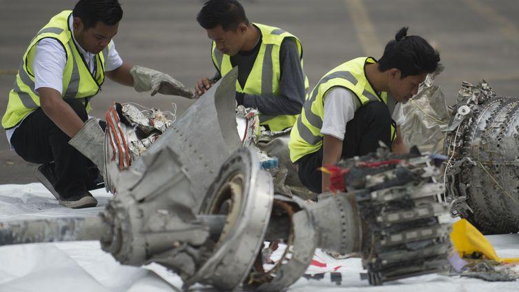 Des enquêteurs examinent des pièces de l'appareil de Lion Air qui a plongé dans la mer le 29 octobre 2018, le 7 novembre 2018 au port de Jakarta (Indonésie). (BAY ISMOYO / AFP)