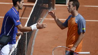 Novak Djokovic etPhilipp Kohlschreiber se félicitent à l'issue de leur match, lundi 3 juin 2013,à Roland-Garros (Paris). (MARTIN BUREAU / AFP)