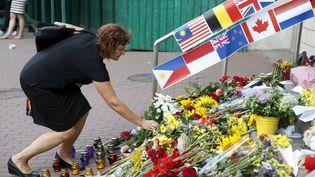 Une femme dépose des fleurs, vendredi 17 juillet 2015, devant l'ambassade des Pays-Bas, à Kiev (Ukraine) en hommage aux victimes du crash de l'avion MH17. (VALENTYN OGIRENKO / REUTERS)