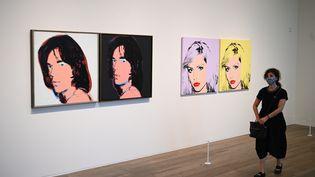 Une visiteuse masquée, virus oblige, passe dans une salle de l'exposition Andy Warhol à la Tate Modern de Londres, le 24 juillet 2020. (DANIEL LEAL-OLIVAS / AFP)