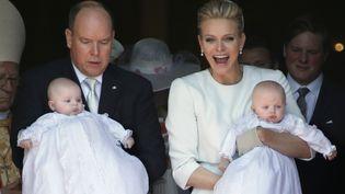 Jacques, prince héréditaire de la principauté de Monaco, et sa sœur Gabriella, dans les bras de leurs parents, le prince Albert II et son épouse Charlène, après leur baptême àla cathédrale de Monaco, le 10 mai 2015. (VALERY HACHE / AFP)