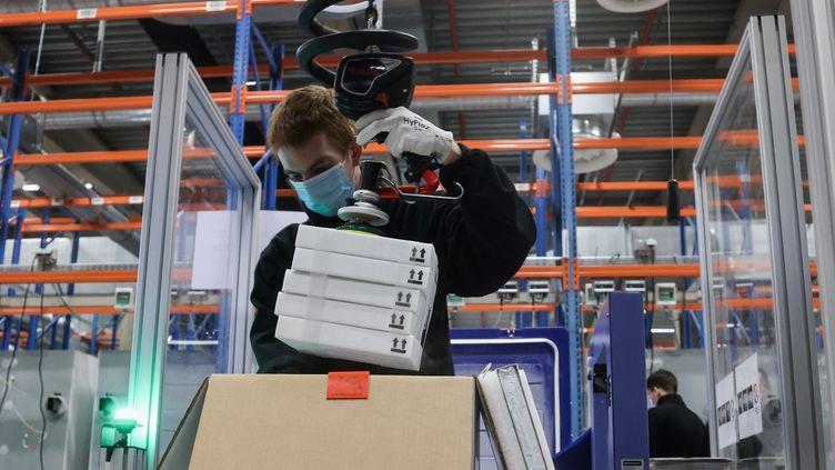 Un employé de Pfizer sur une chaîne de production du vaccin contre le Covid-19 à Puurs (Belgique), le 22 février 2021. (KENZO TRIBOUILLARD / AFP)