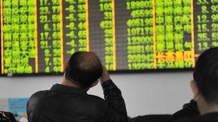 Des investisseurs chinois devant les cours de la Bourse de Shanghai, le 7 janvier 2016, alors que les échanges ont brutalement été arrêtés après une nette baisse de 7% après moins d'une demi-heure. (HU JIANHUANG / IMAGINECHINA / AFP)