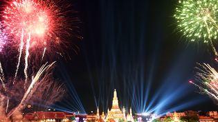 Décor grandiose à Bangkok (Thaïlande), où le feu d'artifice a été tiré devant le temple de l'Aube. (CHRISTOPHE ARCHAMBAULT / AFP)