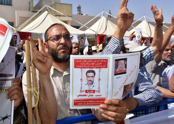 Manifestation à l'extérieur du tribunal de Gabès le 29 mai 2018. Les manifestants portent le portrait de Kamel Matmati, militant islamiste mort sous la torture en 1991. (STRINGER / AFP)