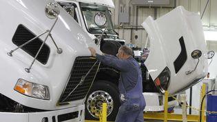 Un employé travaille sur une chaîne de construction de poids lourds dans une usine Volvo à Dublin (Irlande), le 26 janvier 2011. (STEVE HELBER / AP / SIPA)