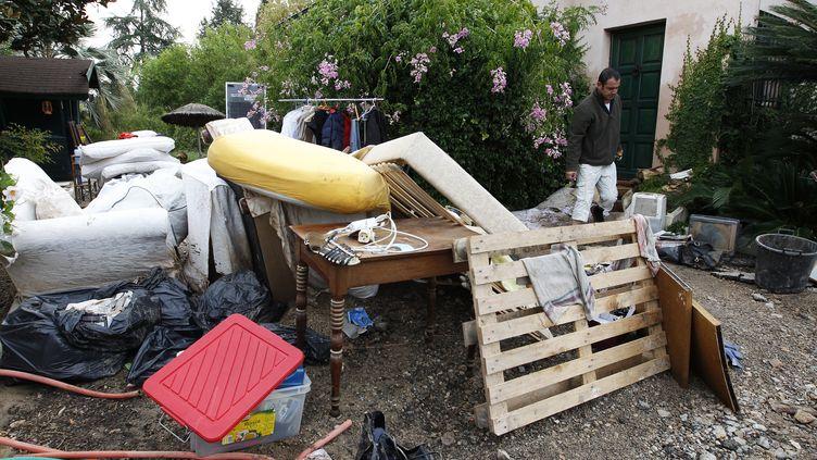 Un homme devant les meubles de sa maison endommagée par les inondations à Antibes (Alpes-Maritimes), le 5 octobre 2015. (JEAN-CHRISTOPHE MAGNENET / AFP)