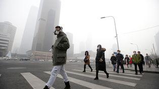 Des passants portant des masques contre la pollution traversent une rue à Pékin, le 21 décembre 2016. (JASON LEE / REUTERS)