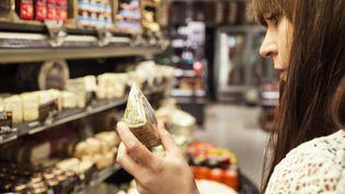 Jeune femme analysant une étiquette de fromage dans un supermarché. (GETTY IMAGES / MASKOT)