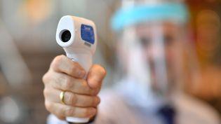 Un membre du personnel portant un écran facial utilise un thermomètre laser pour tester les températures des clients dans un magasin Furniture Village à Croydon, dans le sud-est de Londres le 5 juin 2020. (BEN STANSALL / AFP)