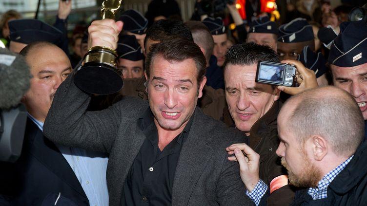 """Jean Dujardin se frayant un chemin à l'aéroport de Roissy, au lendemain du triomphe du film """"The Artist"""" aux oscars, le 28 février 2012. (MARTIN BUREAU / AFP)"""