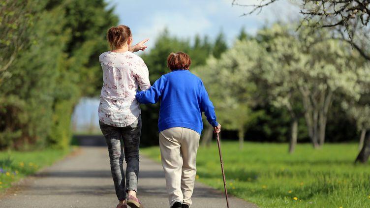 Unedame âgée et dépendante est assistée d'une femme pour faire une promenade. (VANESSA MEYER / MAXPPP)