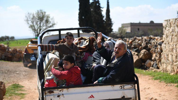 Des civils syriens fuient Afrin, alors que les Turcs attaquent la ville, le 13 mars 2018. (GEORGE OURFALIAN / AFP)