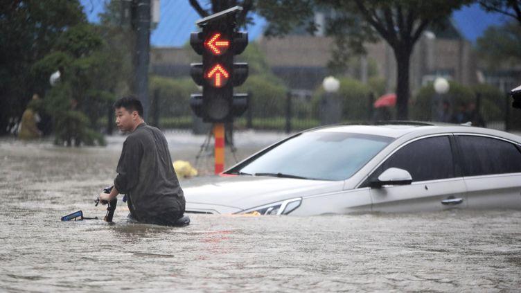 Un homme traverse une route inondéeà Zhengzhou, dans la province d'Henan (Chine), le 20 juillet 2021. (MEITU / CHINATOPIX / AP)