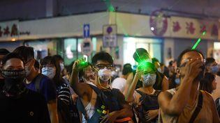 Des manifestants utilisent des pointeurs laser à Hong Kong, le 14 août 2019. (MANAN VATSYAYANA / AFP)