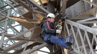 Un peintre au travail sur la Tour Effeil en 2009. (PATRICK KOVARIK / AFP)