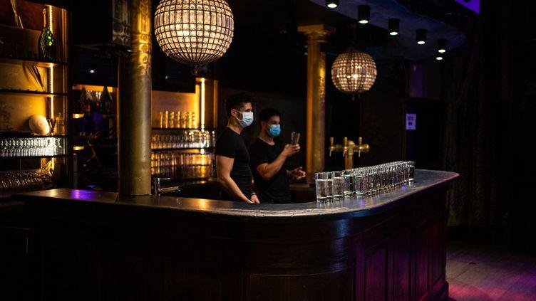 Deux serveurs masqués préparent la réouverture du Divan du monde à Paris le 8 juillet 2021. (XOSE BOUZAS / HANS LUCAS)