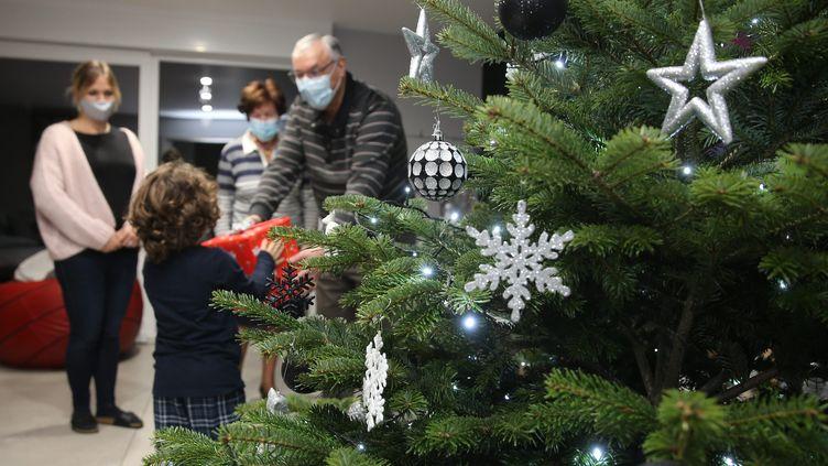 Un enfant reçoit un cadeau de Noël. Photo d'illustration. (JEAN-FRAN?OIS FREY / MAXPPP)