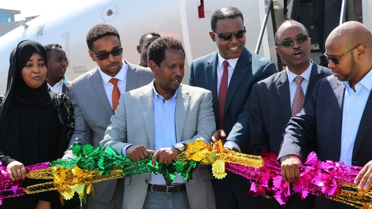 Le maire de Mogadiscio, Abdirahman Omar Osman, au centre de la photo, inaugure le premier vol entre Addis Abebba et Mogadiscio, le 13 octobre 2018. Il est mort dans une attaque suicide perpétrée le 24 juillet 2019 par les islamistes shebab. (ABDIRAZAK HUSSEIN FARAH / AFP)