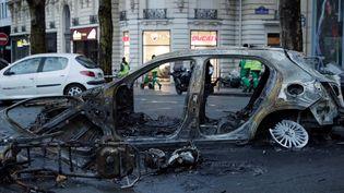 """Une carcasse de voiture dans les rues deParis, au lendemain de la mobilisation des """"gilets jaunes"""", le 2 décembre 2018. (GEOFFROY VAN DER HASSELT / AFP)"""