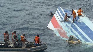 Des plongeurs en train de récupérer une grande partie du gouvernail de l'A330 d'Air France dans l'océan Atlantique, le 1er juin 2009. (HO / BRAZILIAN NAVY / AFP)
