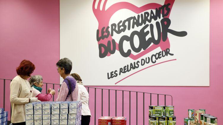 Des bénévoles des Restos du cœur se préparent pour une distribution d'aliments, le 25 novembre 2013, à Paris. (PATRICK KOVARIK / AFP)