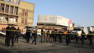 Des forces de sécurité irakiennes autour de laplace Al-Tayaran à Bagdadaprès l'attentat qui a coûté la vie à au moins 26 personnes, le 15 janvier 2018. (SABAH ARAR / AFP)