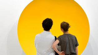 """Un couple contemple le""""Monochrome Yellow"""" (2017) de l'artiste britannique Anish Kapoor avant l'ouverture au public de l'Art Basel de Bâle.  (Fabrice COFFRINI / AFP)"""