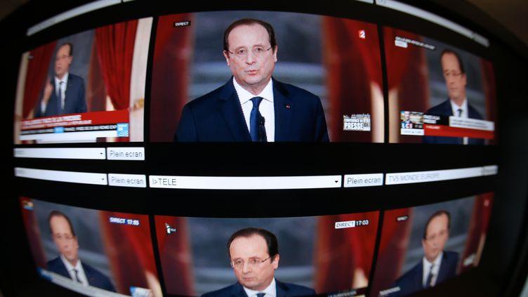 Plusieurs écrans sur lesquels apparaît François Hollande, mardi 14 janvier 2014, lors de sa conférence de presse donnée à l'Elysée (Paris). (THOMAS COEX / FRANCE2/BFMTV/ITELE /FRANCE24 /L)