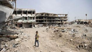Un garçon devant des bâtiments détruits à Mossoul, en Irak, en avril 2017. (CHRISTOPHE SIMON / AFP)