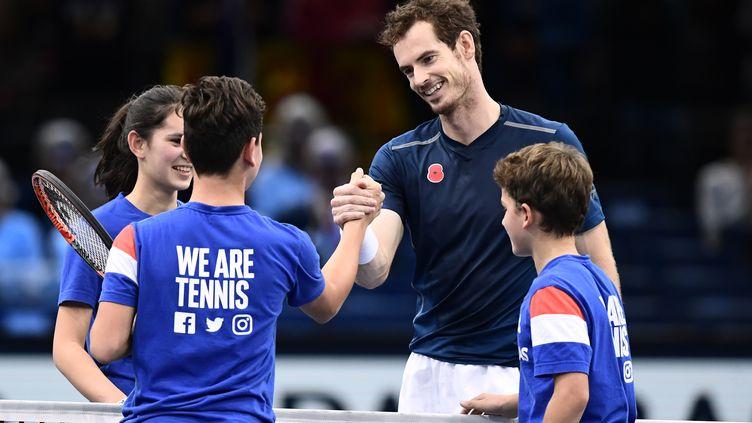 Andy Murray savoure sa couronne en compagnie de jeunes ramasseurs de balle aux anges. (MIGUEL MEDINA / AFP)